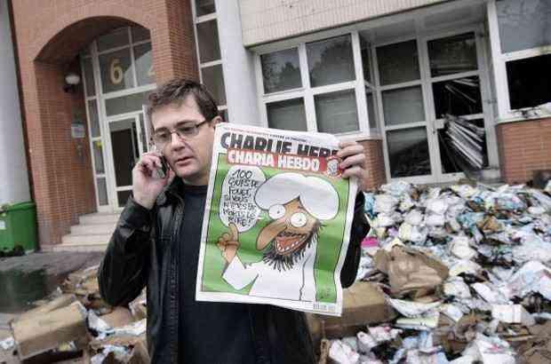 Stéphane Charbonnier davanti alla sede bruciata dalla molotov