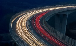Blurred lights of vehicles driving on a tall viaduct with wind barriers, long exposure